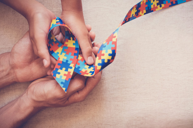 Hands holding puzzle ribbon for autism awareness Premium Photo